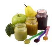 Tres tarros de los alimentos para niños con las cucharas Imágenes de archivo libres de regalías