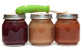 Tres tarros de los alimentos para niños y de la cuchara Imagen de archivo