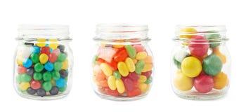Tres tarros por completo de diferentes tipos de caramelos Foto de archivo libre de regalías
