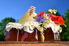 Tres tarros por completo de miel fresca deliciosa, de pedazo de cazo de la miel del panal y de flores salvajes en colmenar Fotografía de archivo