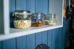 Tres tarros transparentes para la comida en el estante blanco en la cocina imagen de archivo