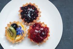 Tres Tarttlets con la crema y las frutas, bayas en la placa redonda blanca sobre fondo oscuro Visión superior Endecha plana foto de archivo