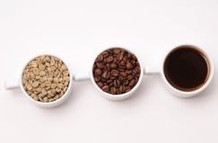Tres tazas blancas con diversas etapas del café: las habas verdes y asadas y alistan la bebida Imagen de archivo libre de regalías