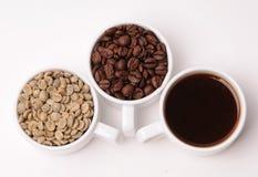 Tres tazas blancas con diversas etapas del café: las habas verdes y asadas y alistan la bebida Imagen de archivo