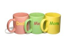 Tres tazas coloridas - papá, yo, mama (familia) Imágenes de archivo libres de regalías