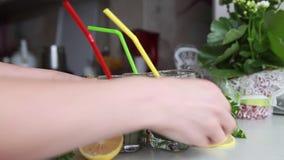 Tres tazas de cóctel verde con los tubos pusieron la tabla con la fruta almacen de video