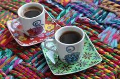 Tres tazas de café brillantes con café express caliente en una superficie colorida Imagen de archivo libre de regalías