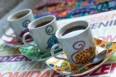 Tres tazas de café brillantes con café express caliente en una superficie colorida Imágenes de archivo libres de regalías