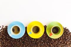Tres tazas de café coloridas en el grupo de granos de café imágenes de archivo libres de regalías