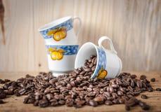 Tres tazas de café decorativas y granos dispersados del café recientemente asado Fotografía de archivo libre de regalías