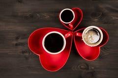 Tres tazas de café en el corazón rojo Imagenes de archivo