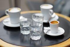 Tres tazas de café fresco en la tabla de café de la calle fotos de archivo libres de regalías