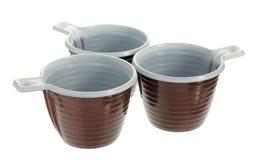 Tres tazas de café marrones plásticas disponibles Foto de archivo