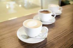 Tres tazas de coffe en línea diagonal Fotografía de archivo libre de regalías