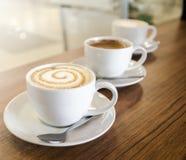 Tres tazas de coffe en línea diagonal Imagen de archivo libre de regalías