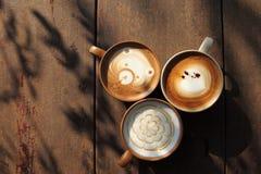 Tres tazas de diverso café que son capuchino, moca y leche del caramelo en la tabla rústica de madera por la mañana con l fuerte imagenes de archivo