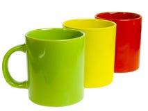 Tres tazas de la te. Rojo, amarillo y verde. Fotos de archivo