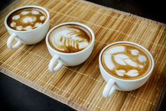 Tres tazas de latte del cafe con tres formas del arte del latte Imagen de archivo libre de regalías