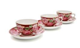 Tres tazas de té con los platillos aislados Imagenes de archivo