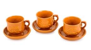 Tres tazas de té de la arcilla con los platillos Foto de archivo