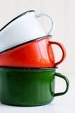 Tres tazas esmaltadas coloridas brillantes Fotografía de archivo libre de regalías