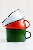 Tres tazas esmaltadas coloridas brillantes Foto de archivo libre de regalías
