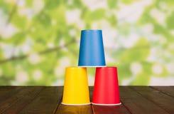 Tres tazas plásticas multicoloras se colocan en uno a, en la tabla de madera foto de archivo libre de regalías