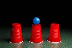 Tres tazas rojas y una bola azul Fotografía de archivo