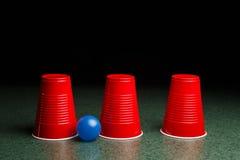 Tres tazas rojas y una bola azul Foto de archivo libre de regalías
