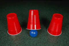 Tres tazas rojas y una bola azul Imágenes de archivo libres de regalías