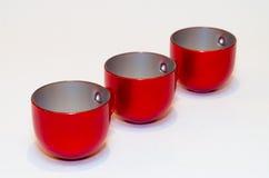 Tres tazas vacías rojas de té (café) en el fondo blanco Fotografía de archivo