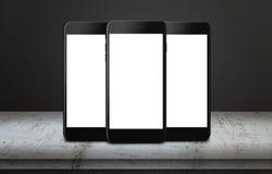 Tres teléfonos móviles en la tabla con la exhibición aislada para la maqueta Imagenes de archivo