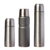 Tres thermoses del metal aislados en blanco fotografía de archivo