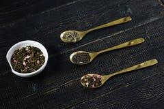 Tres tipos de té en las cucharas - verdes, el negro y Rooibos imagenes de archivo