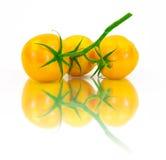 Tres tomates amarillos frescos en un fondo blanco Imagen de archivo libre de regalías