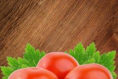 Tres tomates con la hoja en el fondo blanco Foto de archivo libre de regalías