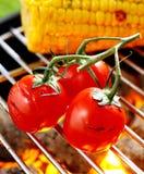 Tomates de cereza que asan a la parrilla sobre un fuego Imagen de archivo libre de regalías