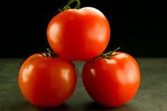 Tres tomates empilados en fondo gris negro Foto de archivo libre de regalías