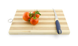 Tres tomates en la rama verde en el escritorio con el isolat del cuchillo Fotos de archivo