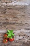Tres tomates en la tabla de madera Fotografía de archivo