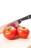 Tres tomates rojos y un cuchillo de acero Fotos de archivo libres de regalías