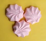 Tres tortas rosadas del merengue en superficie amarilla imagen de archivo