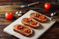 Tres tostadas con los tomates foto de archivo