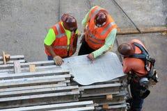 Tres trabajadores con el gráfico Fotos de archivo libres de regalías