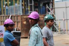 Tres trabajadores de construcción de sexo masculino en un emplazamiento de la obra Imágenes de archivo libres de regalías