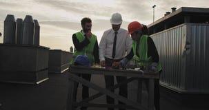 Tres trabajadores de construcción rodean un escritorio que mira los proyectos originales de la construcción, ellos todo el punto  almacen de metraje de vídeo