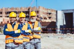 Tres trabajadores de trabajo que presentaban con los brazos cruzaron en fotos de archivo