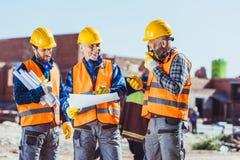 Tres trabajadores en cascos de protección que examinan planes del edificio y que hablan en la radio portátil foto de archivo libre de regalías