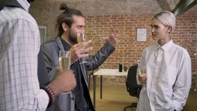 Tres trabajadores multy-étnicos cuentan las historias, lenguaje corporal, sentándose en oficina, champán de consumición, concepto almacen de video