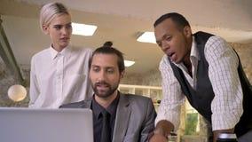 Tres trabajadores multy-étnicos discuten la idea en el ordenador portátil, concepto coworking, concepto de la comunicación almacen de metraje de vídeo